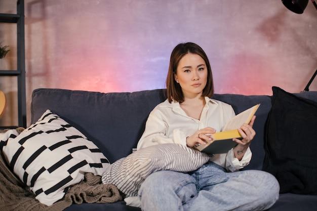 Giovane ragazza asiatica che legge un libro. la ragazza è seduta sul divano. camera accogliente.