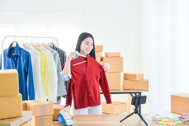 Giovane ragazza asiatica che vende vestiti online in live streaming