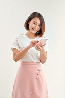 Giovane studentessa asiatica con zaino tenere il telefono cellulare isolato su sfondo bianco.