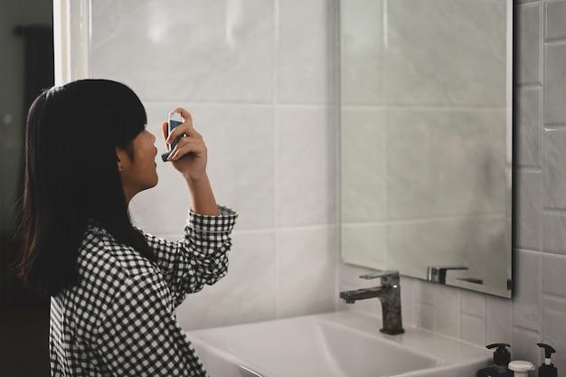 Giovane ragazza asiatica che usa l'inalatore per l'asma per il trattamento inalatorio delle malattie respiratorie.