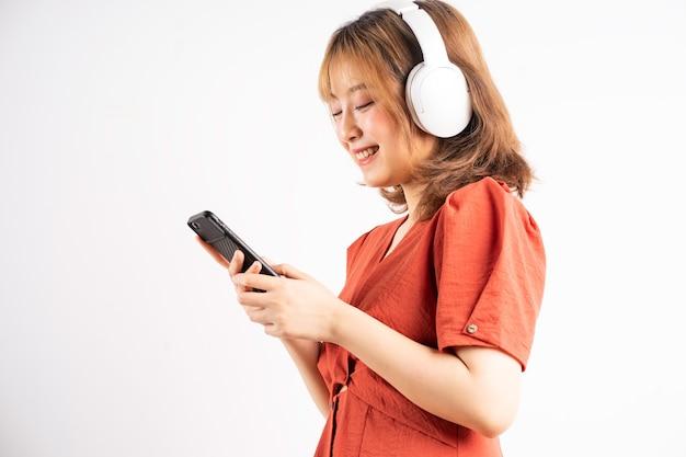 Giovane ragazza asiatica che usa il telefono e indossa le cuffie per godersi la musica