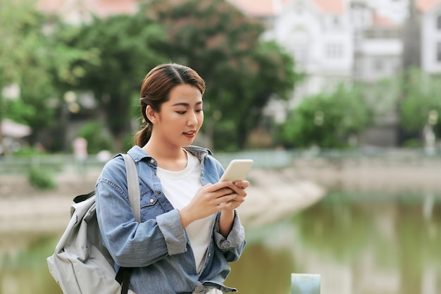 Giovane ragazza asiatica che usa lo smartphone in giardino