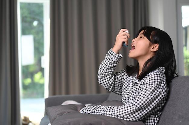 Giovane ragazza asiatica con asma che usa l'inalatore per l'asma per prevenire gli attacchi sul divano.