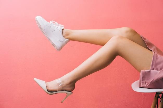 Giovane ragazza asiatica con un piede che indossa scarpe da ginnastica e un piede che indossa tacchi alti