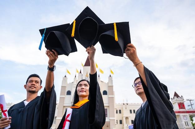 Giovani laureati asiatici che tengono i cappelli di laurea