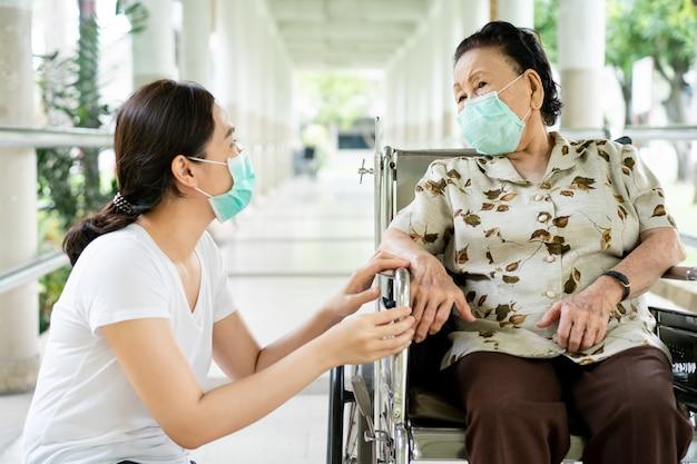 Giovane nipote asiatico che si prende cura di sua nonna che si siede sulla sedia a rotelle.