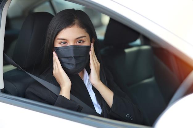 Giovane donna in buona salute asiatica in vestito nero da affari con maschera protettiva per l'assistenza sanitaria in automobile e guida di auto. nuovo concetto di allontanamento normale e sociale
