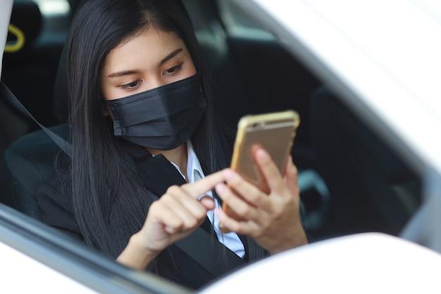 Giovane donna asiatica in buona salute in abito nero da lavoro con maschera protettiva per l'assistenza sanitaria in automobile e utilizzando smartphone e guidando l'auto. nuovo concetto di distanza normale e sociale