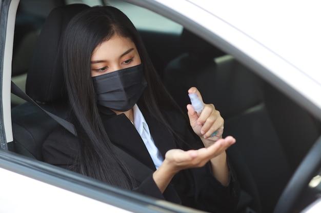 Giovane donna in buona salute asiatica in vestito nero da affari con maschera protettiva per uso sanitario disinfettante per mani con spray alcol per l'igiene in automobile e guida di auto. nuovo concetto di allontanamento normale e sociale