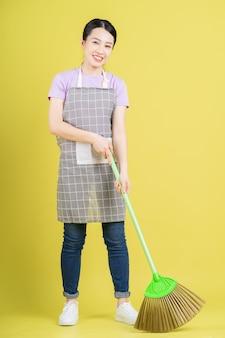 Giovane casalinga asiatica in posa su sfondo giallo