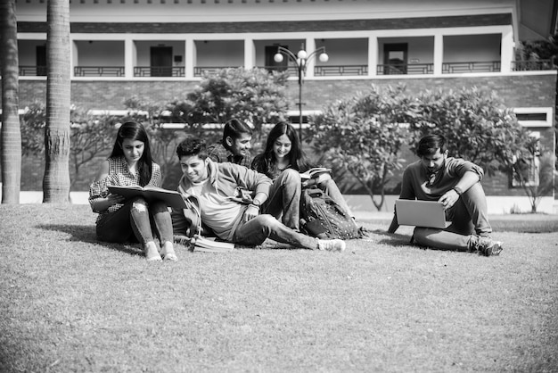 Giovani studenti universitari indiani asiatici che leggono libri, studiano sul laptop, si preparano per l'esame o lavorano su un progetto di gruppo mentre sono seduti sull'erba, sulle scale o sui gradini del campus universitario