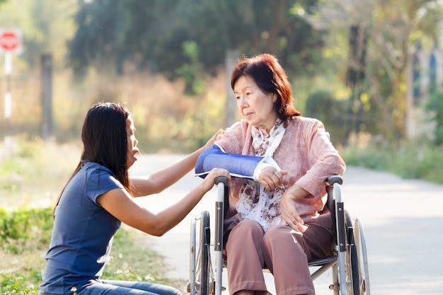 Il giovane asiatico si prende cura della donna anziana, thailandia