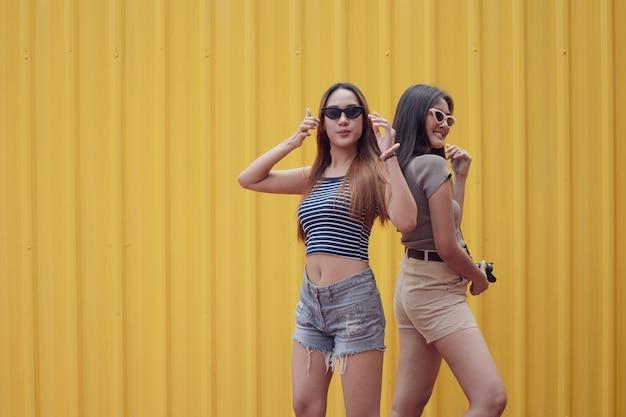 Giovani donne asiatiche gioiose delle coppie nella suite di moda estiva in piedi nella parete di lamiera di acciaio gialla.