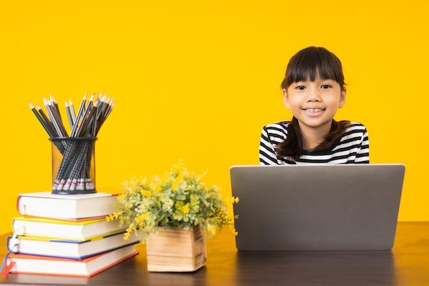 Giovane bambino asiatico, studio tailandese della ragazza sulla tavola con il computer portatile, imparante online su fondo giallo