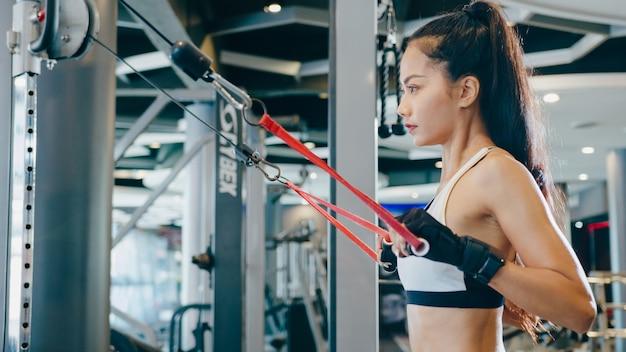 Giovane donna asiatica esercizio facendo esercizio-macchina cavo crossover bruciare i grassi allenamento in classe di fitness