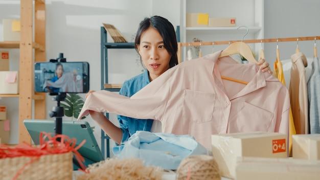 Stilista di moda giovane signora asiatica utilizzando il telefono cellulare che riceve l'ordine di acquisto e mostra i vestiti in live streaming