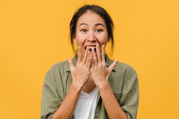 La giovane donna asiatica si sente felice con l'espressione positiva, gioiosa sorpresa funky, vestita con un panno casual isolato sul muro giallo. la donna felice adorabile felice si rallegra del successo.