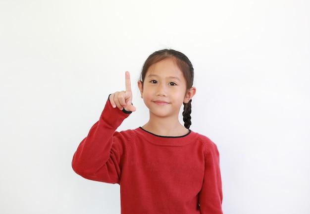 Giovane bambina asiatica che indica il dito indice in su su bianco
