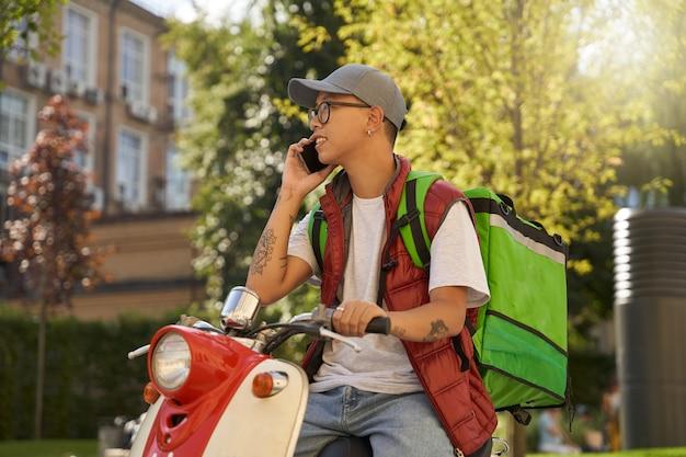 Giovane corriere maschio asiatico con borsa termica che parla al telefono con c
