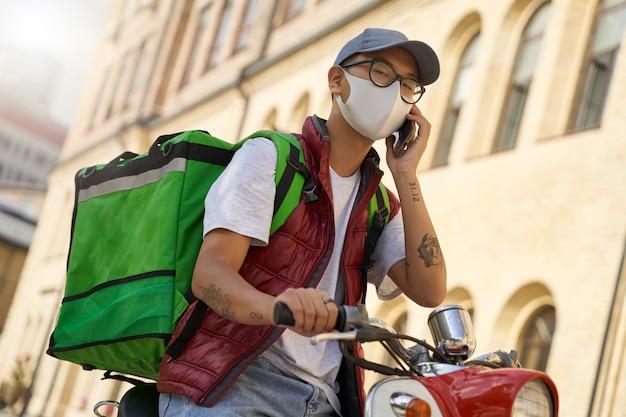 Giovane corriere maschio asiatico con borsa termica che indossa una protezione per il viso