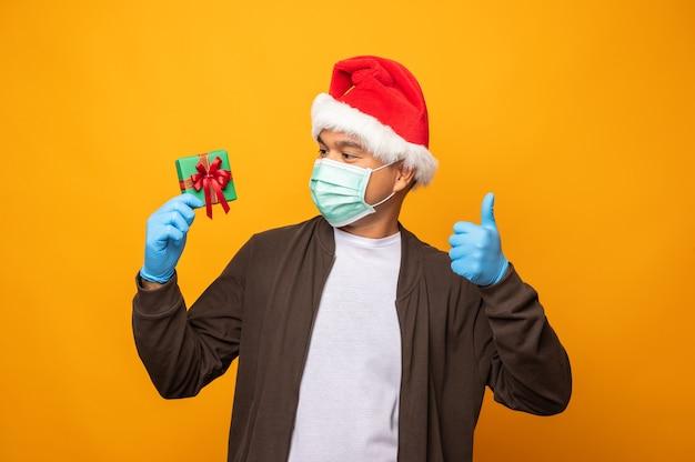 Giovane uomo asiatico il giorno di natale che tiene una confezione regalo