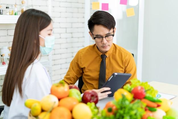Il giovane asiatico viene a incontrare il nutrizionista in ospedale e parla di dieta e alimentazione. nutrizionista esperto che dà una raccomandazione alimentare a un uomo che ha problemi di salute.