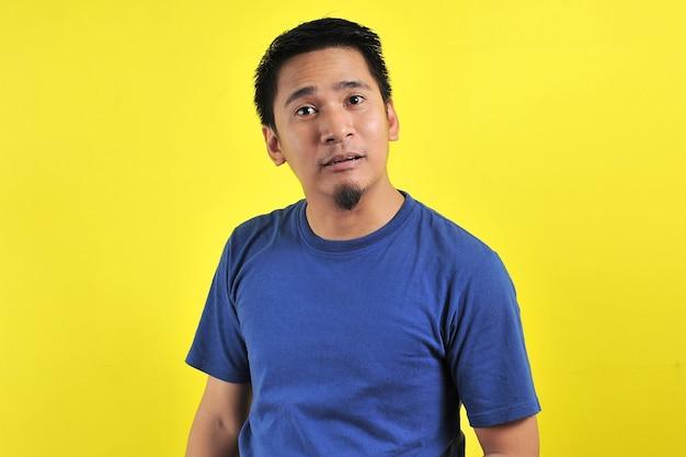 Giovane uomo asiatico che fa un gesto divertente con la bocca, isolato su sfondo giallo