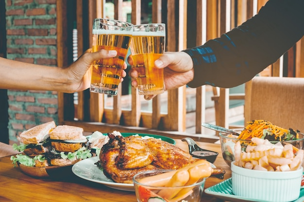 Giovane uomo asiatico bere bicchieri di birra e clink felice mentre godendo la festa a casa