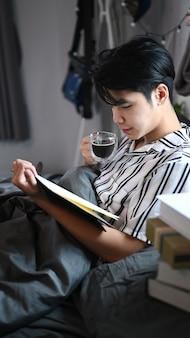 Giovane uomo asiatico che beve caffè e legge un libro sul letto al mattino.