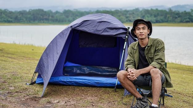 Il giovane uomo asiatico gode del campeggio al bacino idrico