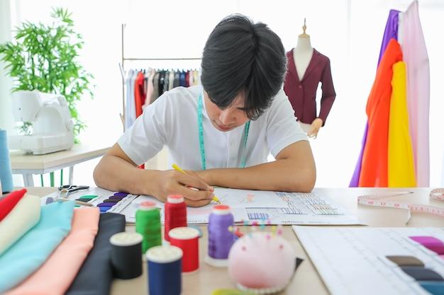 Giovane uomo asiatico che tiene matita e disegno modello schizzo alla scrivania in atelier.