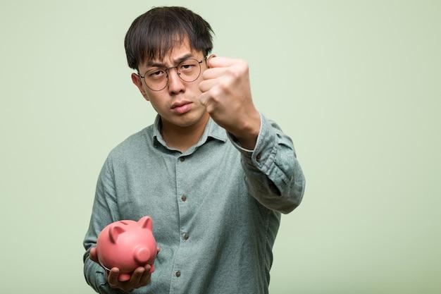 Giovane uomo asiatico che tiene un salvadanaio che mostra il pugno alla parte anteriore, espressione arrabbiata