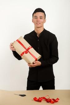 Il giovane uomo asiatico tiene un pacco regalo nelle mani - immagine