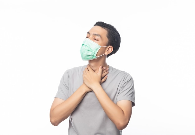 Giovane uomo asiatico in maschera igienica che soffre di mal di gola, 2019-ncov o coronavirus. malattie respiratorie sospese nell'aria come il combattimento e l'influenza del pm 2.5. colpo dello studio isolato sulla parete bianca