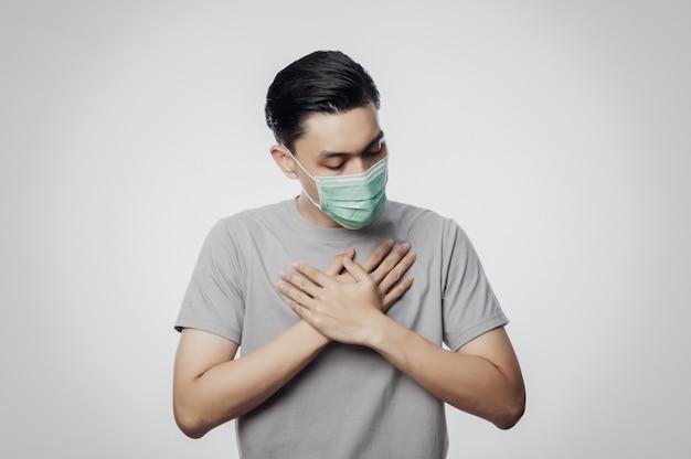 Giovane uomo asiatico in maschera igienica che soffre di mal di gola, 2019-ncov o coronavirus. malattie respiratorie sospese nell'aria come il combattimento e l'influenza del pm 2.5. colpo dello studio isolato su bianco
