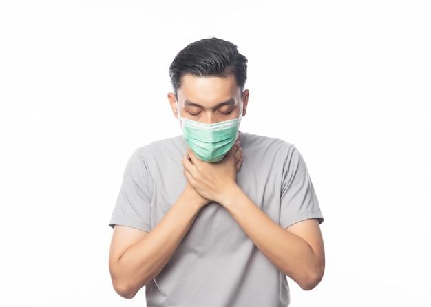 Giovane uomo asiatico in maschera igienica che soffre di mal di gola, 2019-ncov o coronavirus. malattie respiratorie sospese nell'aria come il combattimento e l'influenza del pm 2.5.