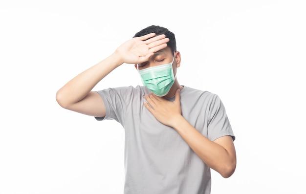 Giovane uomo asiatico in maschera igienica che soffre di mal di gola e che ha influenza, 2019-ncov o coronavirus. malattie respiratorie sospese nell'aria come il combattimento con pm 2.5. colpo dello studio isolato sulla parete bianca