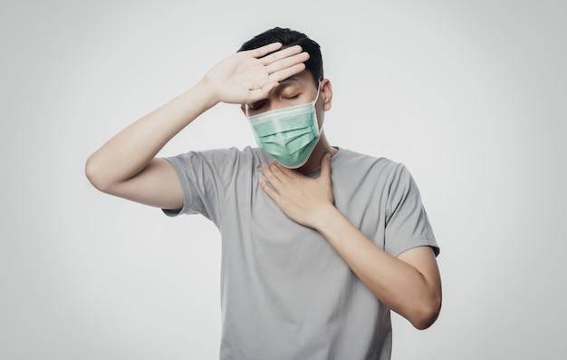 Giovane uomo asiatico in maschera igienica che soffre di mal di gola e che ha influenza, coronavirus. malattie respiratorie sospese nell'aria come il combattimento con pm 2.5. colpo dello studio isolato su fondo bianco.