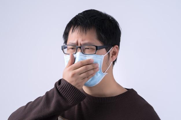 Il giovane asiatico sta tossendo, non si sente bene, vomita male indossando una maschera facciale blu medica isolata su sfondo bianco, primo piano, copia spazio.