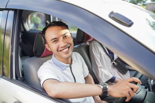 Un giovane asiatico che ride guardando la telecamera mentre guida un'auto