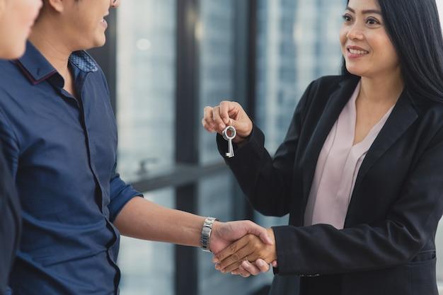 Giovane uomo asiatico che stipula un contratto con l'agenzia di vendita di case immobiliari, agente femminile che stringe la mano a un uomo caucasico per ottenere il contratto e la chiave della casa