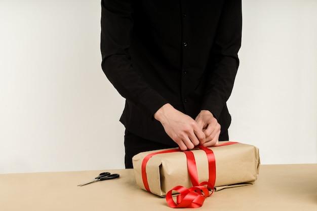 Giovane uomo asiatico confeziona un pacco regalo sul tavolo - immagine