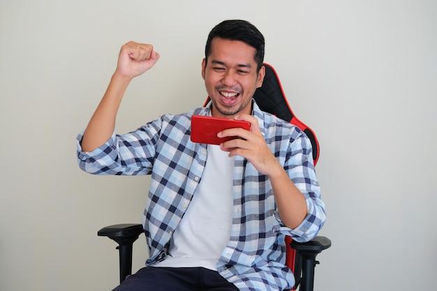 Giovane uomo asiatico che gioca al gioco mobile mentre è seduto sulla sedia da gioco che mostra un gesto vincente