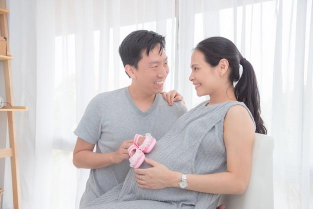 Il giovane uomo asiatico ha messo le scarpe di bambino rosa sulla sua pancia incinta della moglie e sorride