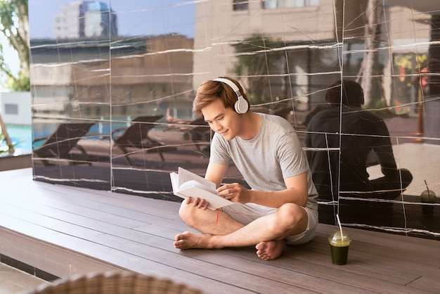 Giovane uomo asiatico che legge un libro e ascolta musica a bordo piscina in una soleggiata giornata estiva