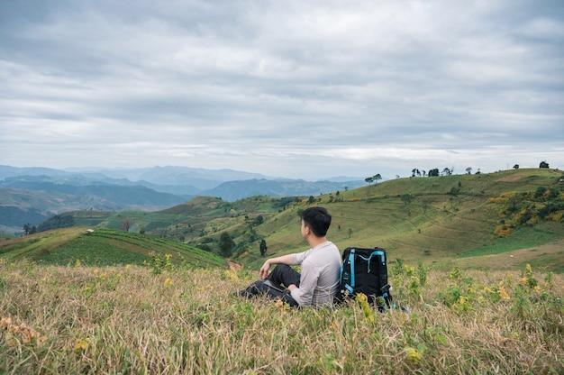 Giovane uomo asiatico che si rilassa con la borsa della macchina fotografica sulla collina del terreno coltivabile in rurale