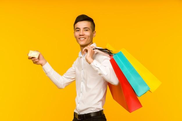 Giovane uomo asiatico che mostra la sua borsa della spesa e la carta di credito su sfondo giallo
