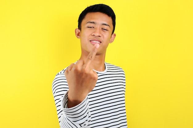 Giovane uomo asiatico che mostra il dito medio facendoti fottere cattiva espressione, provocazione e atteggiamento maleducato, isolato su sfondo giallo