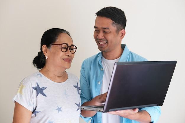 Giovane uomo asiatico che mostra qualcosa usando il suo laptop a una donna anziana