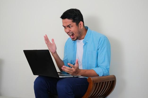 Giovane uomo asiatico seduto su una sedia e guardando il suo laptop con espressione di rabbia